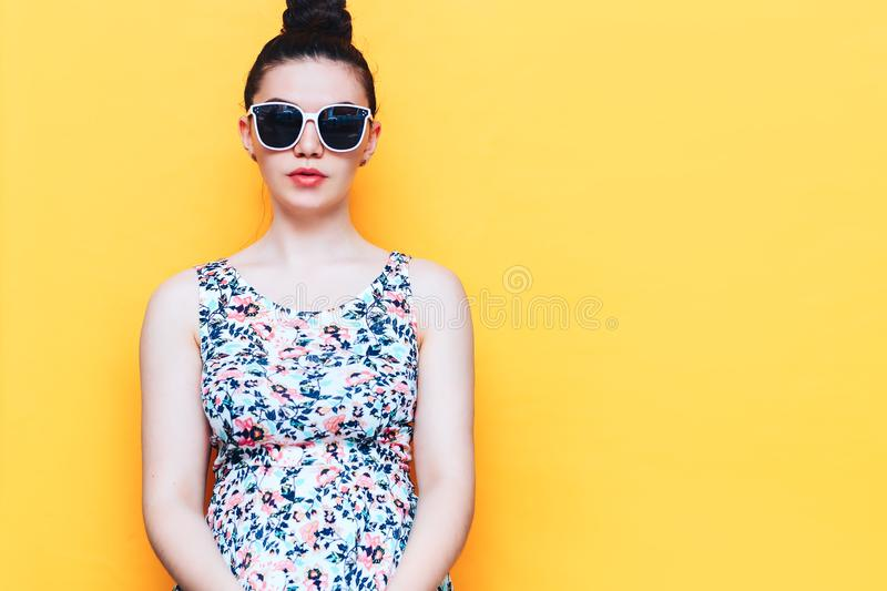 Happy beautiful yound woman in dress and white sunglasses on yellow background stock photos