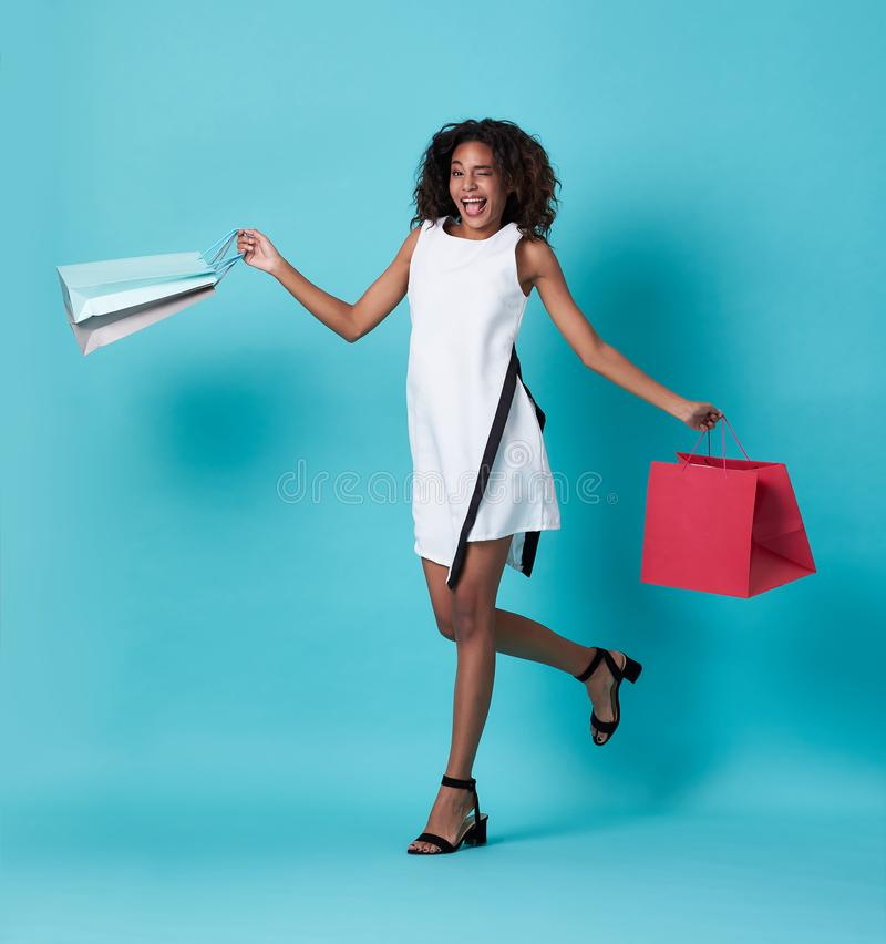 Happy beautiful young african woman in white dress and hand holding shopping bag jumping  over blue background stock images