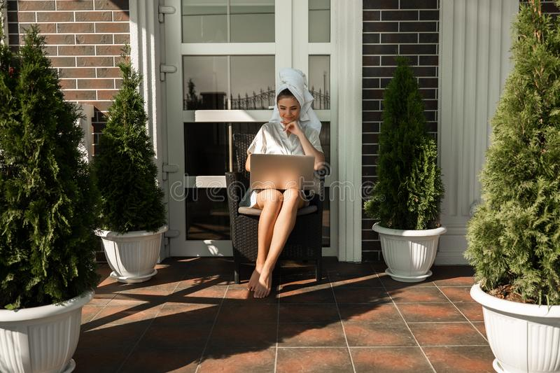 Happy beautiful young brunette woman wearing dressing gown and white towel working in her laptop from home sitting on the terrace royalty free stock photo