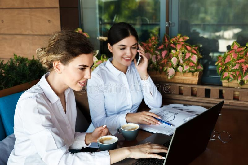 Happy beautiful young businesswomen working on laptop and drinking coffee stock image
