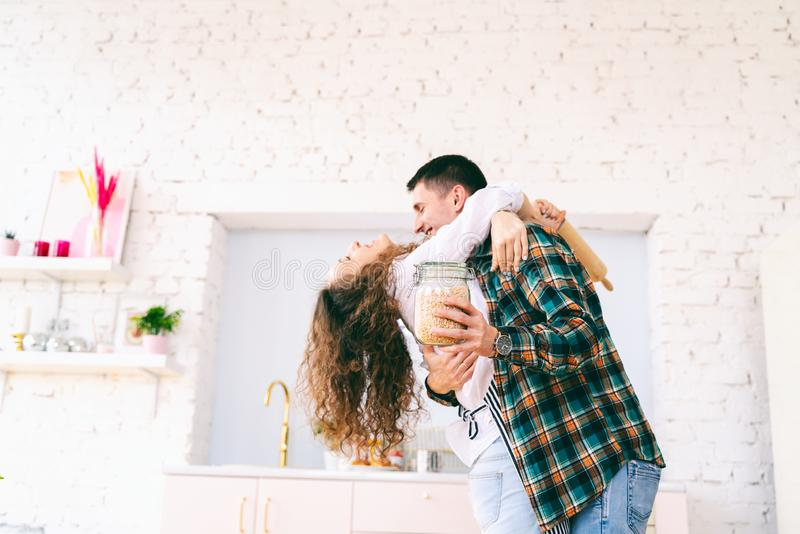 Happy beautiful young couple have fun in the kitchen, dancing, cuddling, cooking food together stock images