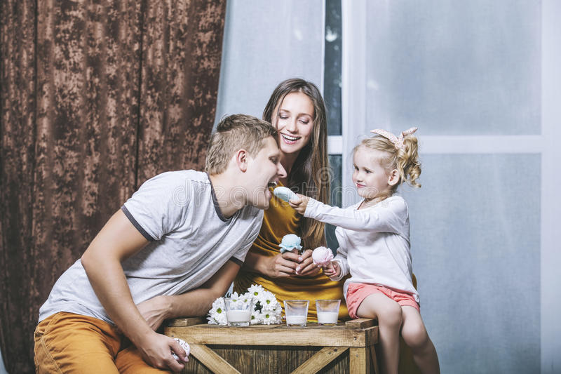 Happy beautiful young family father, mother and daughter drink m royalty free stock photography