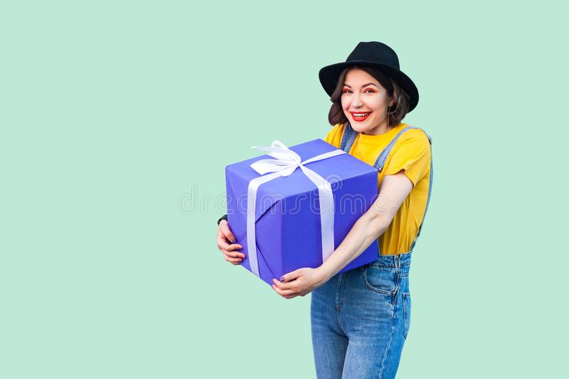 Happy beautiful young girl in fashionable hipster wear in denim overalls and black hat standing and holding big heavy gift box stock photo