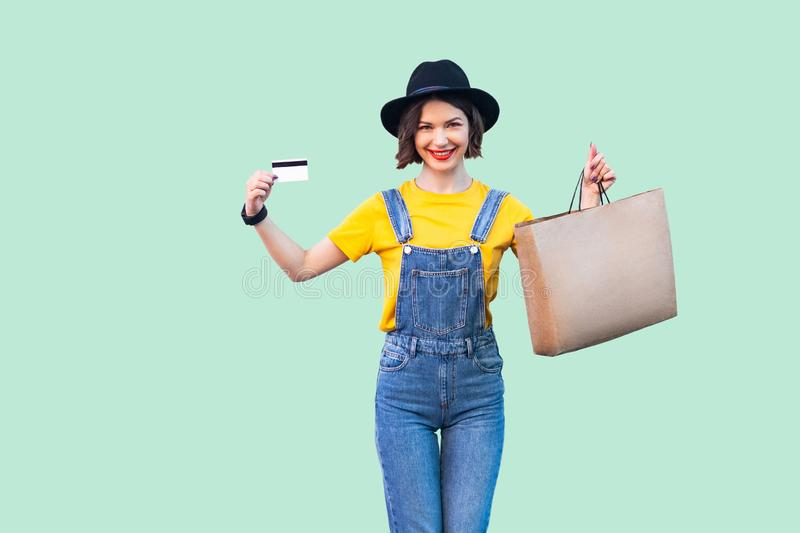 Happy beautiful young girl in hipster wear in denim overalls and black hat holding bank card and shopping bag with toothy smile, royalty free stock photos