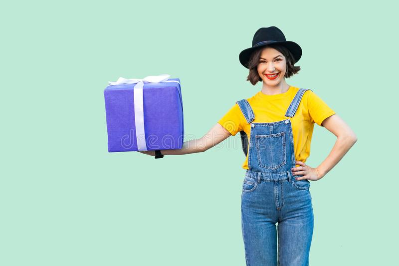 Happy beautiful young girl in hipster wear in denim overalls and black hat standing and holding big heavy gift box with toothy stock images