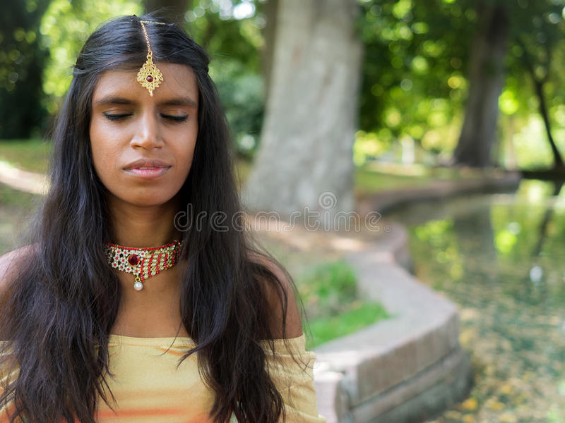 Happy beautiful young indian woman practicing meditation in the royalty free stock images