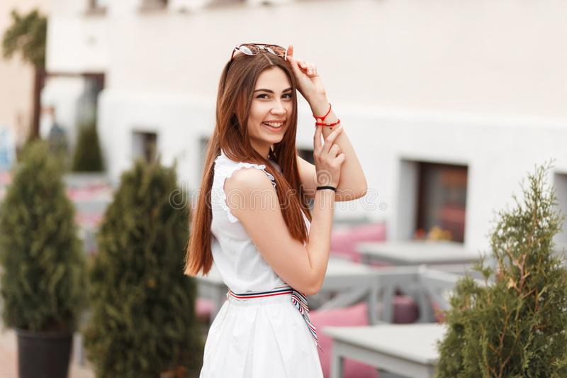 Happy beautiful young model woman in white dress posing outdoors. stock image