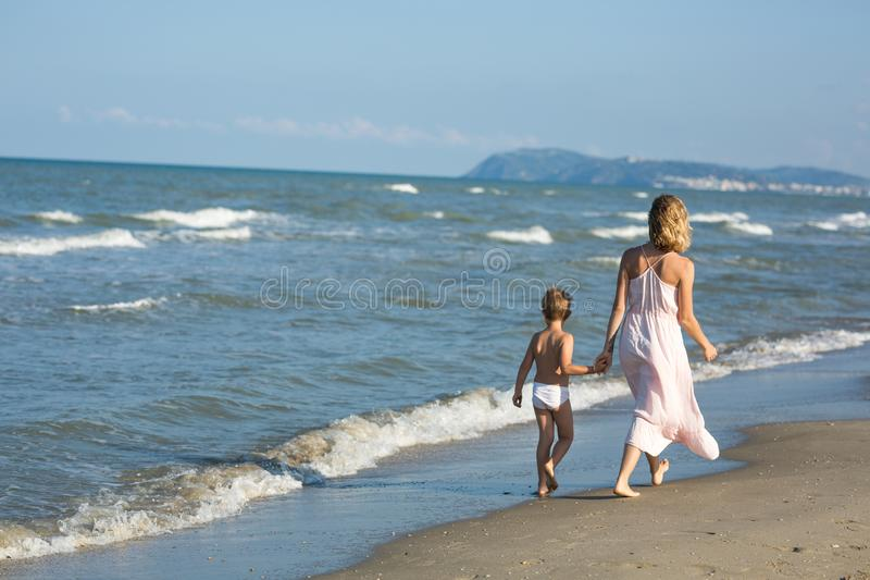 Happy beautiful young mom and child walk far away along the sea stock photos