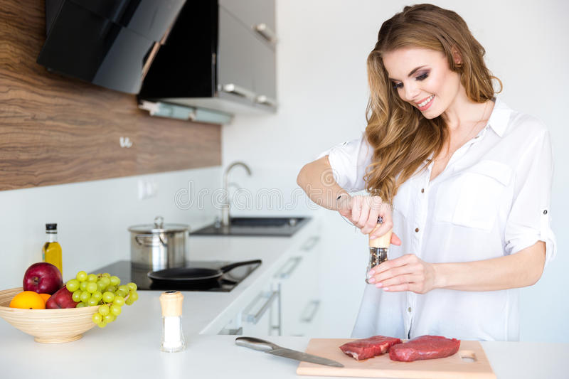 Happy beautiful young woman cooking meat on the kitchen. Happy beautiful young woman in white shirt cooking meat on the kitchen at home royalty free stock photos