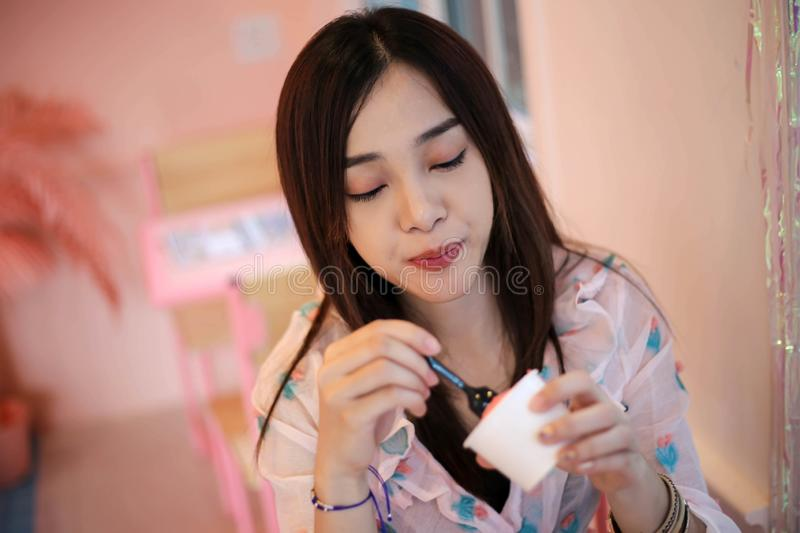 Happy Beautiful young woman eating ice cream,delicious, enjoying, happiness, smiling concept stock image