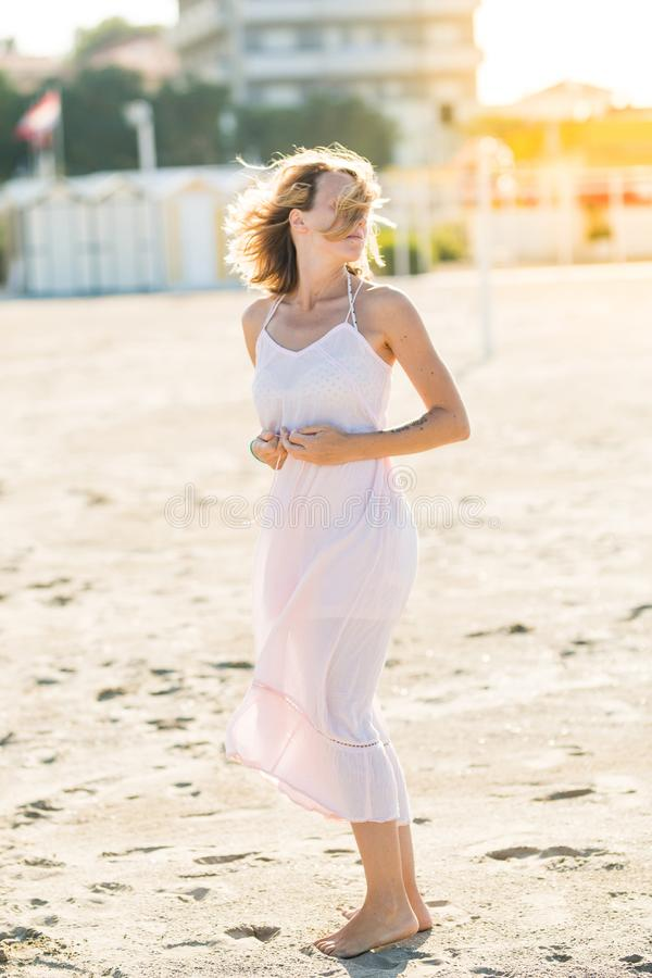 Happy beautiful young woman enjoying sun and wind at the sand beach royalty free stock images