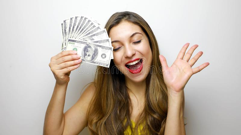 Happy beautiful young woman with eyes closed cover her face with dollars isolated on white background stock photos