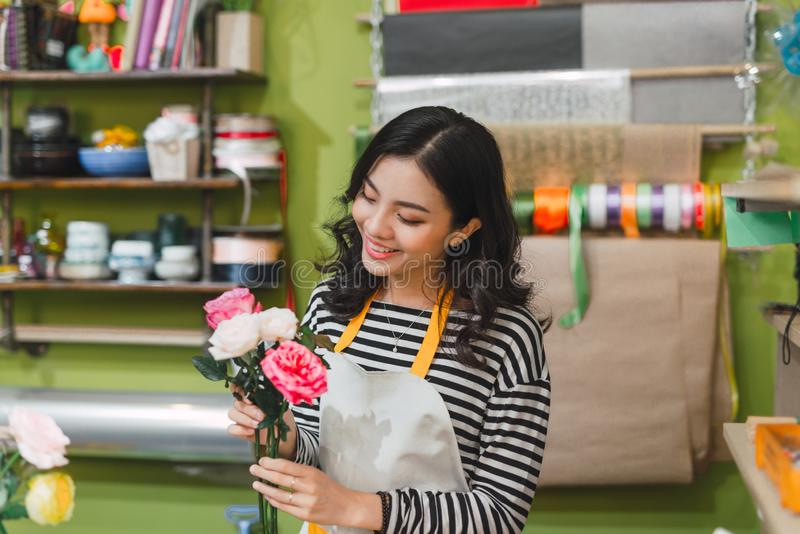 Happy beautiful young woman florist  standing in flower shop royalty free stock image