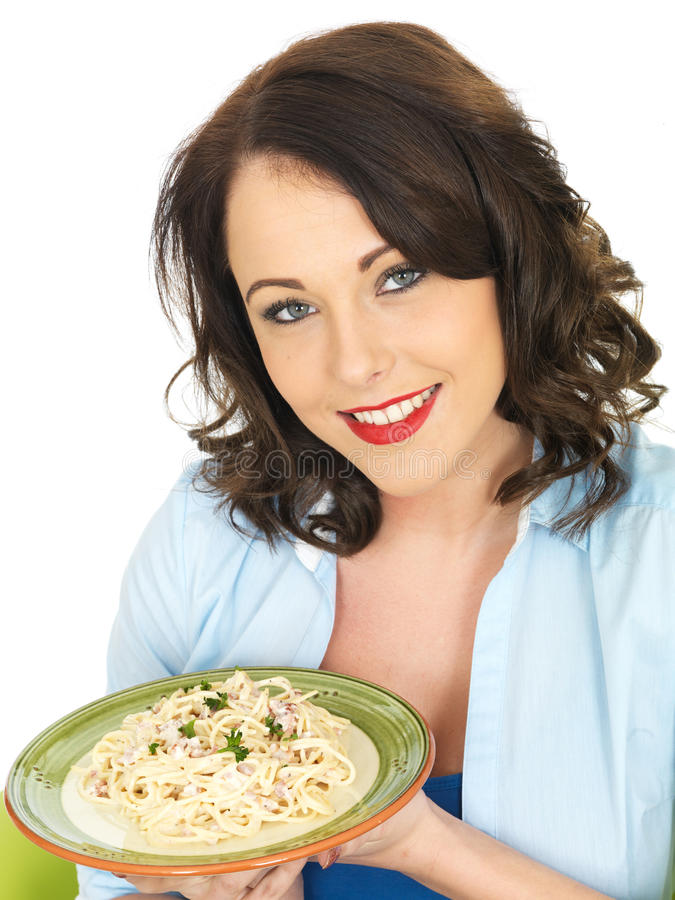 Happy Beautiful Young Woman Holding a Plate of Spaghetti Carbonara Pasta. Happy Beautiful Young Woman, in Her Twenties, Holding a green and white Plate of stock photo