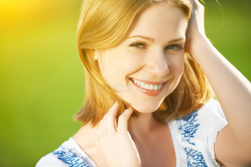 Happy beautiful young woman laughing and smiling on nature. In green royalty free stock images