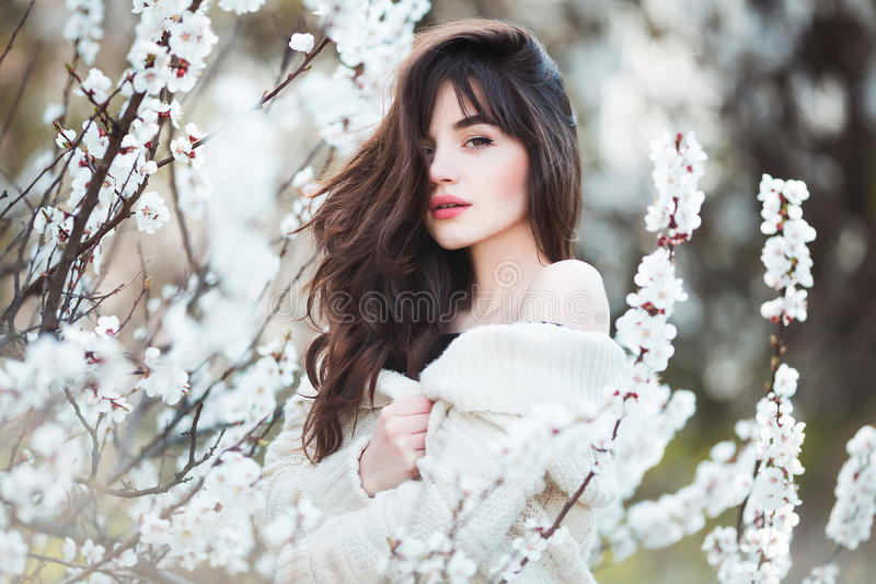 Happy beautiful young woman with long black healthy hair enjoy fresh flowers and sun light in blossom park. Happy beautiful young woman with long black healthy royalty free stock images