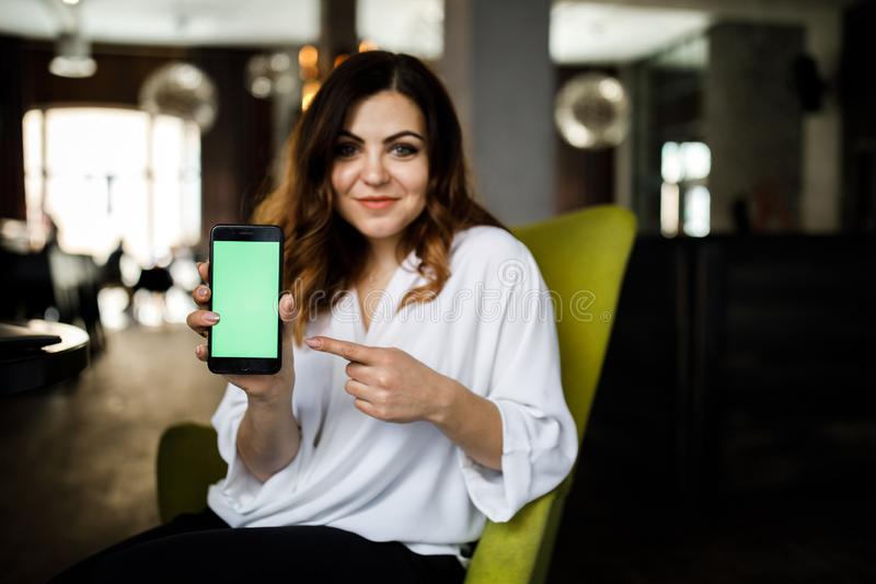 Happy beautiful young woman with long hair holding blank screen mobile phone and pointing finger. Startup, entrepreneur working stock photo