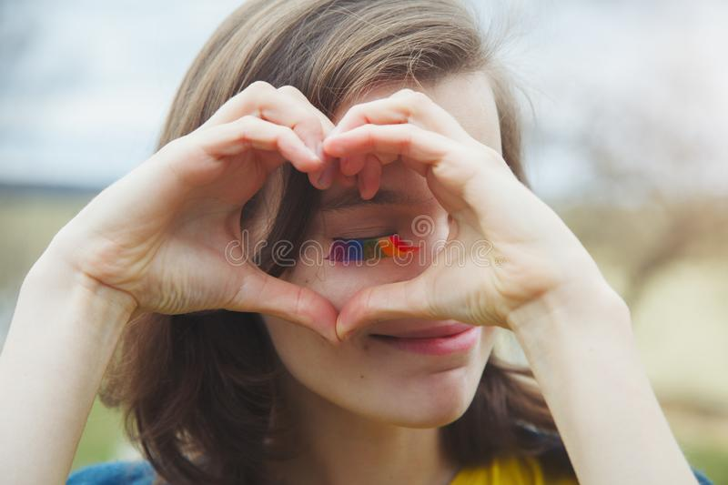 Happy beautiful young woman with rainbow lgbtq eyelashes making heart sign with her hands stock images