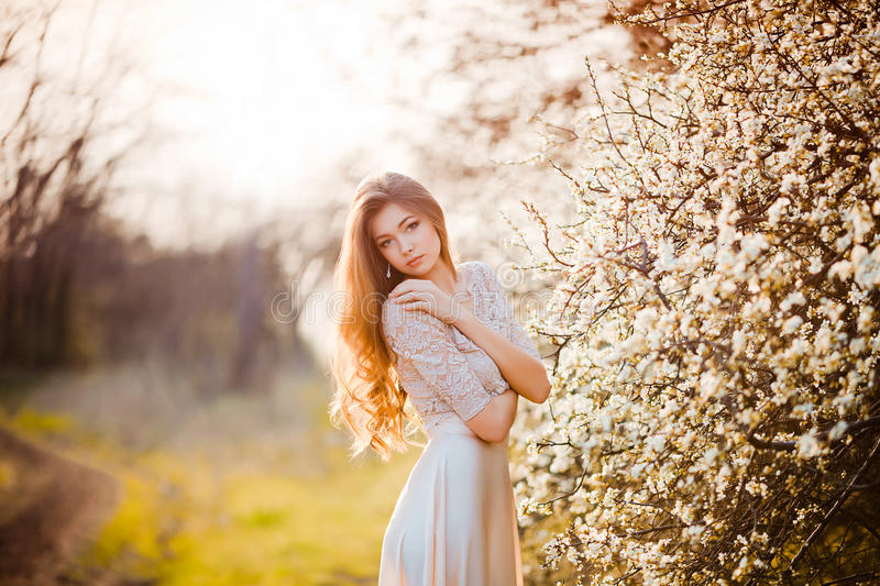 Happy beautiful young woman relaxing in blossom park. royalty free stock photo