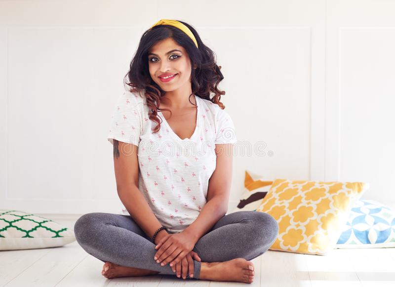 Happy and beautiful young woman sitting on the floor, ready for yoga class stock photography