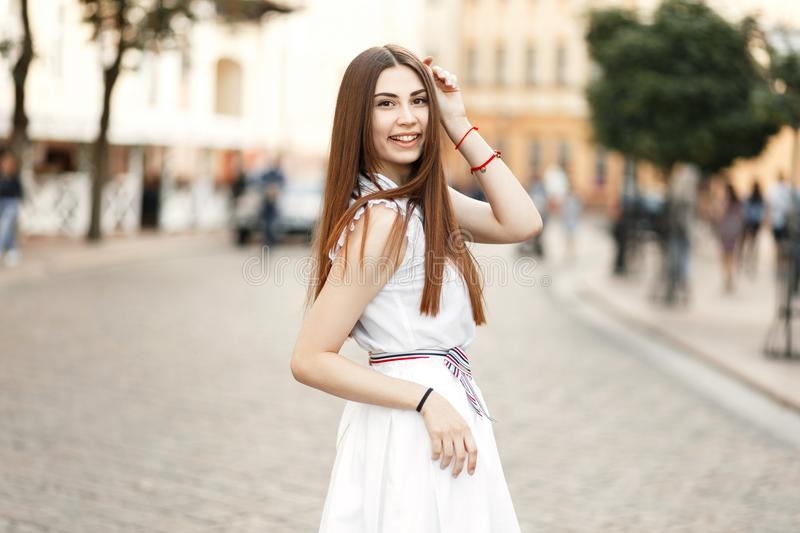 Happy beautiful young woman with smile in white dress stock photo