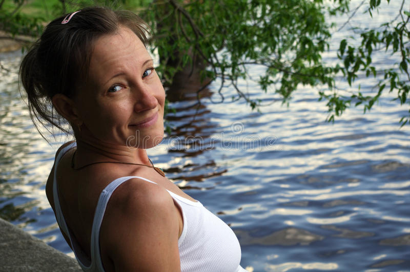 Happy beautiful young woman smiling and looking at camera, standing near water on lake stock photography
