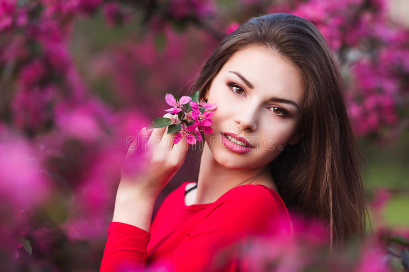 Happy beautiful young woman in spring blossom park. Attractive female in red dress enjoy spring fresh pink flowers stock photos
