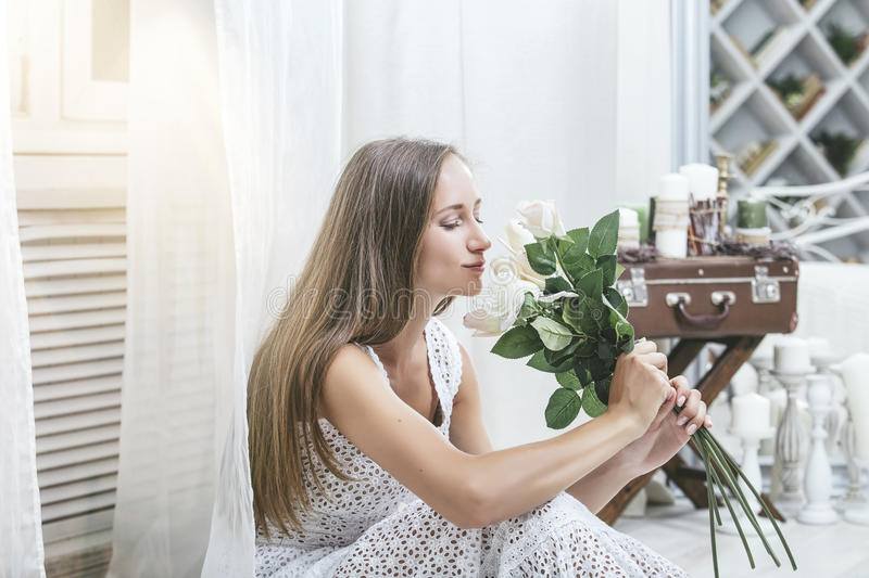 Happy beautiful young woman in a white dress at home with a bouquet of flowers stock photography