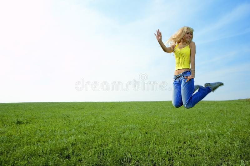 Happy beauty young woman jump in field royalty free stock photography