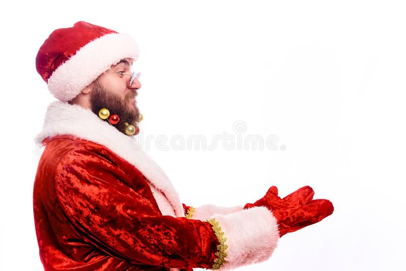 Young emotional bearded man in a Christmas costume. Happy in bespectacled Santa Claus with decorations in a real beard showing empty copy space on the open hand stock photos