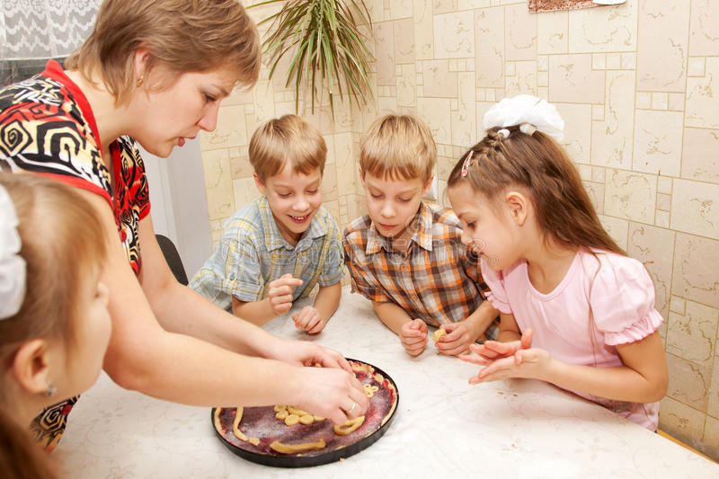 Happy big family cooking a pie together. royalty free stock image