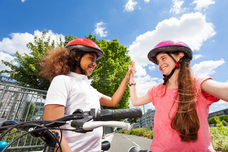 Happy bike riders giving high five after racing stock image