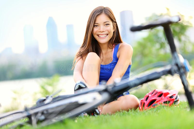 Happy biking woman going road bike. Woman going biking on road bike. Smiling sport fitness model smiling outside in city park in Montreal, Quebec, Canada stock photography