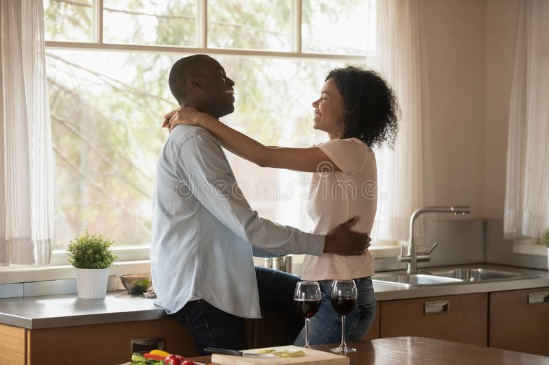 Happy biracial couple hug having romantic date at home stock photography