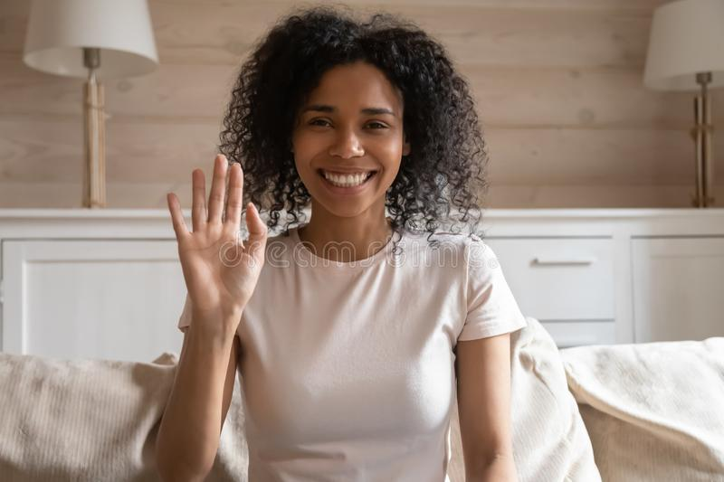 Happy biracial woman wave talking on video call. Smiling african American young woman sit on couch wave greeting with subscribers shoot vlog, happy biracial girl royalty free stock image