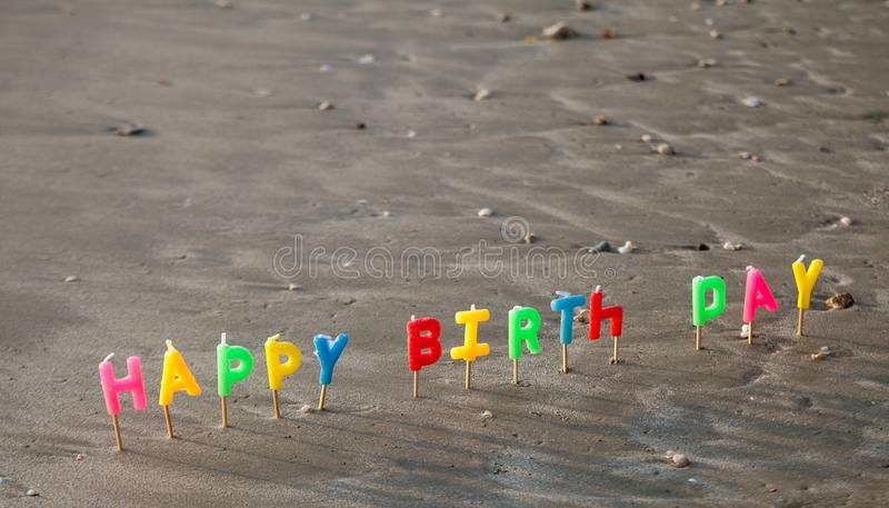 Happy birth day letter candles in the sand. With the sea stock photography