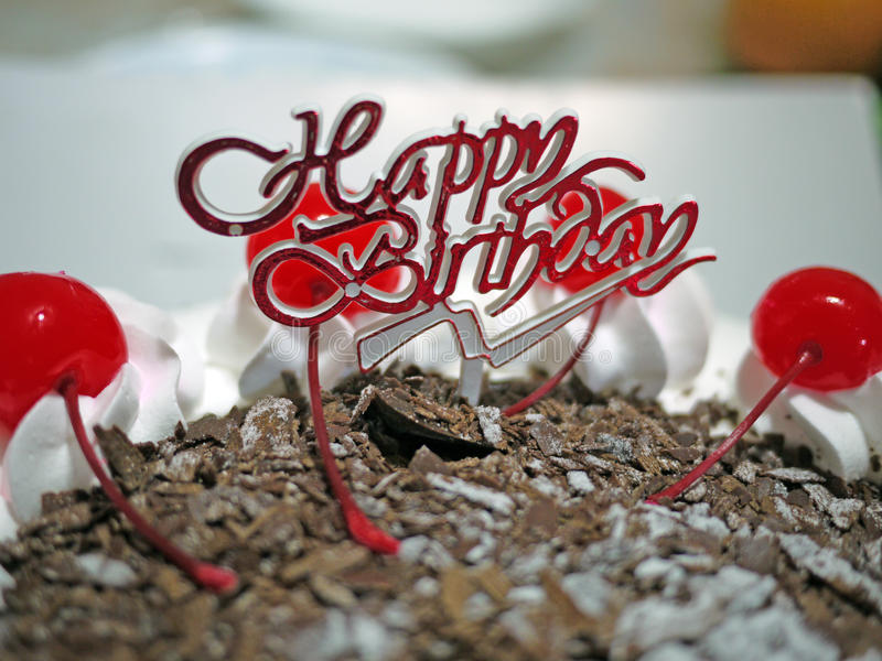 Happy Birthday. Chocolate cake decorated with cherries and chocolate flakes royalty free stock images