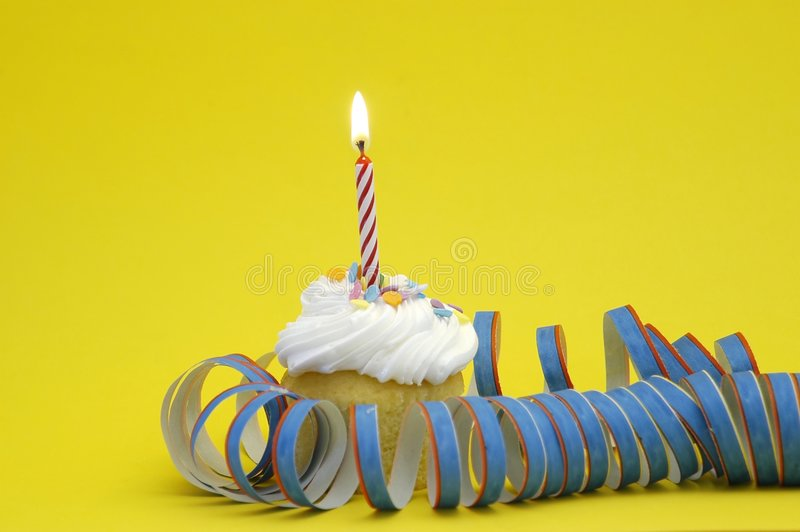 Happy Birthday 2. Cupcake with frosting and burning red candle against yellow background. Surrounded by party decoration royalty free stock images