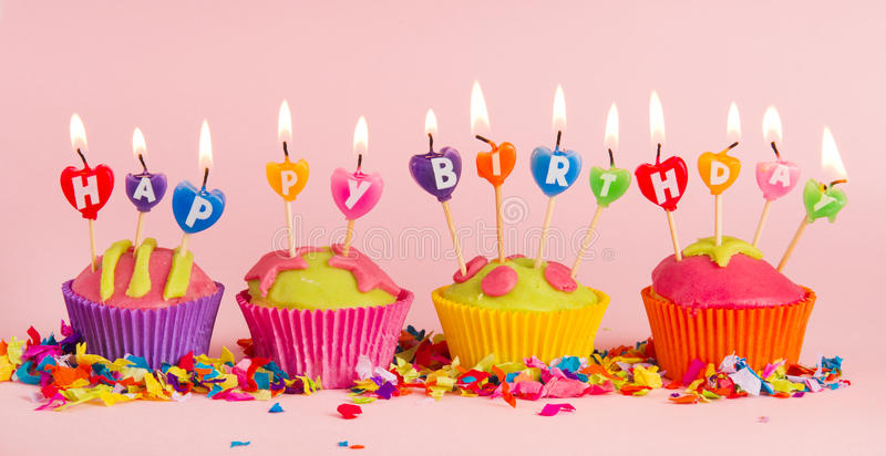 Happy birthday. Cup cakes with burning happy birthday candles stock photography
