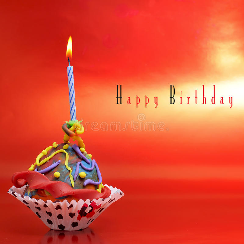 Happy birthday. A plasticine cupcake with a candle on a red background with sentence happy birthday stock photography