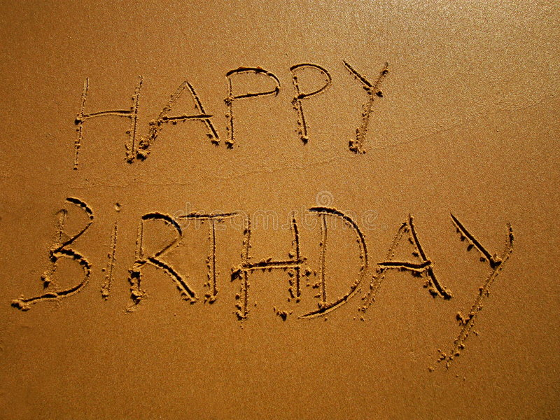 Happy birthday. Message written on the sand stock image