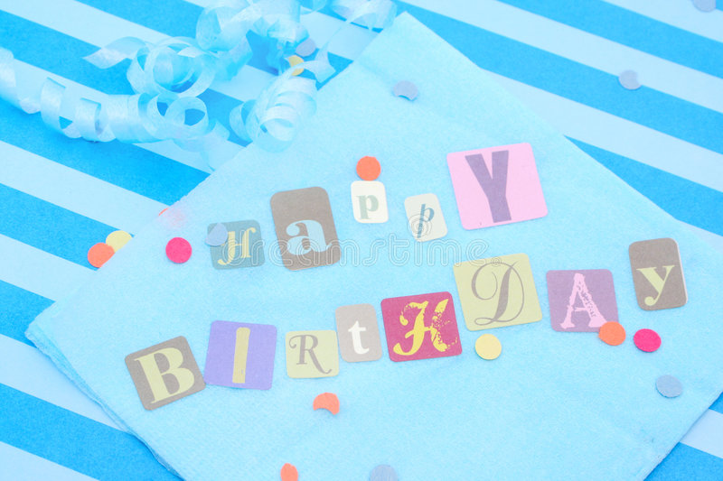 Happy birthday. Cut out letters on blue napkin with ribbons and confetti stock photos