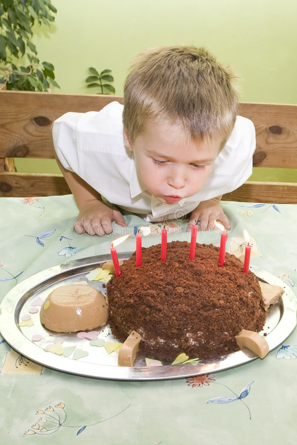 Happy birthday. Little boy is blowing birthday candles stock photography