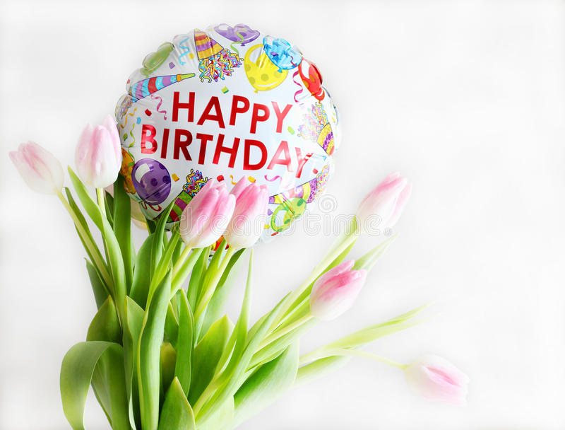 Happy Birthday background. Bouquet of pink tulips and Happy Birthday balloon on a white background. Good for greeting card royalty free stock photography