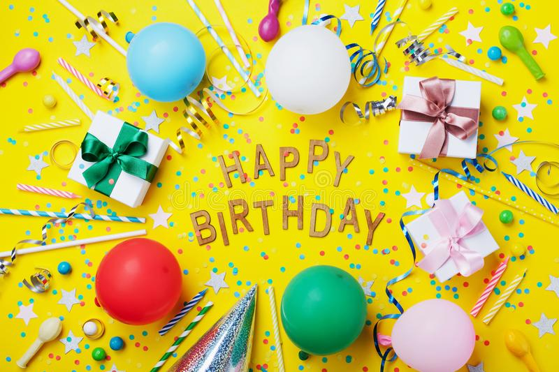 Happy birthday background or greeting flyer. Colorful holiday supplies on yellow table top view. Flat lay style. Happy birthday background or greeting flyer royalty free stock photos