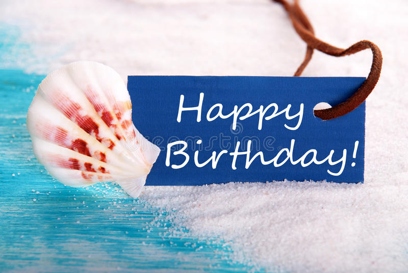 Happy Birthday in Beach Background. Blue Label with Happy Birthday on it at the Beach royalty free stock photos