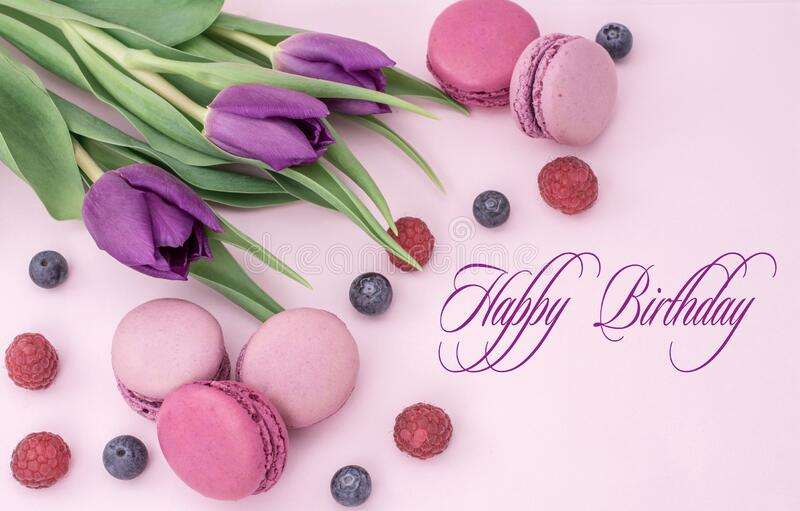 Happy birthday. Beautiful tulips with colourful biscuits macaroon and blueberry raspberry. Happy birthday.. Background, bakery, beautiful, beauty, blue stock photography