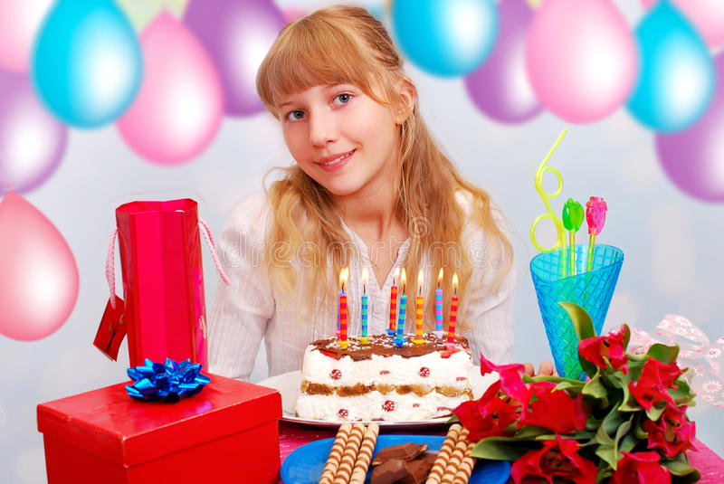Happy birthday. Beautiful young girl celebrates birthday sitting at the party table with cake royalty free stock photo