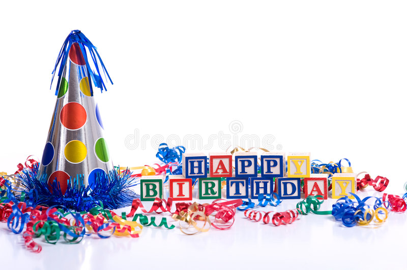 Happy Birthday Blocks. On a white background with copy space, including a party hat and streamers royalty free stock images