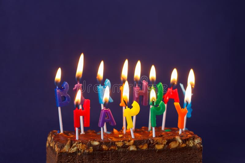 Happy Birthday Brownie Cake with Peanuts, Salted Caramel and Colorful Burning Candles on the Violet Background. Copy Space for. Text lighted unlighted royalty free stock photography